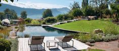 Das Holzdeck und die geschwungene Form des Schwimmteichs passt sich an die vorhandenen Strukturen an und verbindet die fantastische Aussicht mit dem Garten.