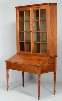 """Greene County, Tennessee two-part walnut bookcase & desk (sometimes called a Plantation Desk). Upper case with ogee cornice over two glazed doors, each with 8 panes, three interior shelves aligned with transoms. Lower desk section has fall front writing section with interior bank of pigeonholes & one dovetailed drawer. Turned legs ending in double ring turned spikes. Poplar secondary. 83 7/8"""" H x 44 1/2"""" W x 25"""" D. Circa 1840 ."""