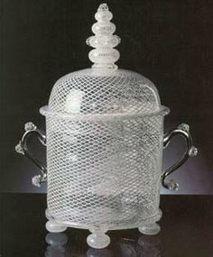 Covered reticello vase, or compote dish, in netted filigree of milk glass and crystal, with ball feet in netted filigree blown glass and handles and cover finial decorated with crystal strawberries. The piece is a reproduction of an early 18th c. model.