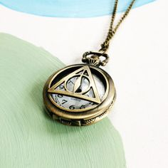 GET YOUR GEEK ON!  Fans of Harry Potter and the Deathly Hallows should recognize this nifty antique brass, Deathly Hallows inspired time piece. Perfect for costume, cosplay, steampunk or as just an unique addition to any memorabilia collection. The piece itself is quite heavy weighing 39 grams, the watch is 5.5cm length and 4cm wide and sits on a 40cm length match chain. Watch is made by Quartz and comes working with battery.  These time pieces make lovely gifts for men & women and might be…