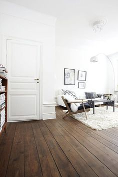 White walls, dark wood floors, mid century furniture. ... contrasting lighter rug.