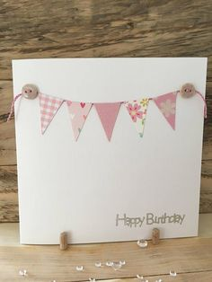 This pretty handmade Birthday Card features bunting cut from shades of pink patterned card and is finished with pink glitter string, polka dot buttons and a silver foil Happy Birthday sentiment. The card has a luxury linen feel and would be suitable for any age. All the cards in my