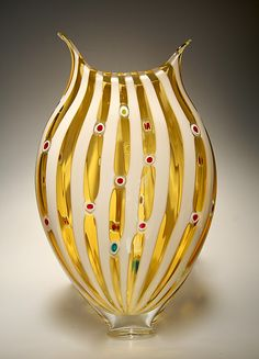 """Almond/Amber Foglio"" Art Glass Vessel Created by David Patchen Elegant Foglio-series work using cane and murrini techniques to create distinct stripes and colored windows. This work features almond opal stripes with stripes of transparent amber glass with murrine windows in assorted colors. This piece is double-encased with thick clear glass so it is significant and stable."