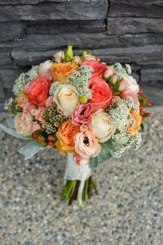Coral, Orange, Champagne Roses, Pink & Green Spray Roses, White Wax Flower, White Queen Anne's Lace, Blush Anemones, Red Hypericum, Broad Leaf Dusty Miller, Hand Tied With White Lace