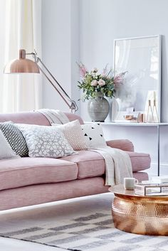 Layer soft rose pink with grey, choose a classic sofa as the room's centrepiece, then introduce pattern with decorative cushions and a rug. Contrast the soft colours with a statement floor lamp and coffee table.