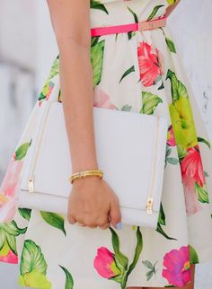 Bright tropical floral fit and flare dress paired with a simple white clutch and gold accessories