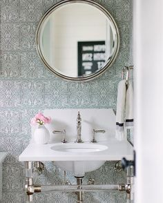 Soft beautiful powder room with blue patterned wallpaper and an acrylic base console sink.