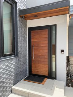 This is our beautiful custom entry door in mahogany wood within a black frame and sidelight with clear low e glass. We ship everywhere! Call us today for a quote Modern Entrance Door, Modern Exterior Doors, Wood Exterior Door, Modern Front Door, Front Door Entrance, Exterior Front Doors, House Front Door, House Entrance, Wood Front Doors