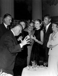 """Alfred Hitchcock entertains his cast from """"To Catch a Thief"""" (left to right) John Williams, Jessie Royce Landis (behind AH), Charles Vanel, Grace Kelly, Cary Grant, Brigitte Auber [1955]"""