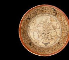 5/ MAYA - Plat polychrome de style codex. C récent, 600-900. Plat creux à bordure rouge. Jeune ♂ richement paré émerge de la tête d'un monstre décharné, lié à l'env aquatique (lignes, cercles = bulles, triangle noir = coquillage en coupe). Perso souligne axe vertical; végétaux (feuilles ondulantes des épaules, nénuphar émerge du crâne, fleur) l'axe horizontal. 4 motifs en quinconce = points cardinaux. Paroi interne : 4 crânes (même axe des quadrilobes). Vagues, bulles et nymphées = monde…