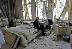 Mohammed Mohiedin Anis, also known as Abu Omar, 70, smokes his pipe as he sits in his destroyed bedroom, listening to music on his hand-cranked gramophone in Aleppo's formerly rebel-held al-Shaar neighborhood in Syria.