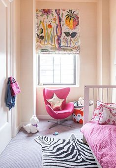 A Roman shade crafted from Josef Frank fabric hangs over a sleek, child-size egg chair in younger daughter Daisy's room.