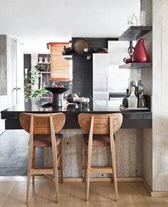 La cocina abierta tiene un mesón de granito brasilero, color negro. Se destacan las sillas recicladas de los años cincuenta y los objetos de La Chamba.
