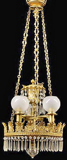 """A rare Anglo-American prism-hung gilt-bronze and brass three-light argand chandelier, early 19th century, each arm retaining a plate reading """"J I Cox New York"""" the peeiod anthemion-modeled canopy supporting period chainsjoined to the anthemion-mounted ring adorned with drop prisms around the perimeter, the ring with a looking glass base, ormolu and crystal finial, the period font joined to three arms, each retaining their period fitter rings, now with frosted glass globes. circa 1801-1840"""