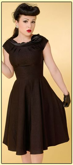 Simple and elegant best describe this cute little black dress. The rounded neckline is pleated and the black satin collar is adorned with a black satin rosette. The sleeves are also accented with black satin. The dress has a fitted waist, swing skirt and back zip. Pair this with some gloves for a full vintage look.