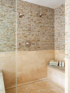 Tile tips:Small details make this shower a standout space. Two showerheads placed higher and lower on the wall accommodate bathers of different heights. The intricately planned tiles create a visually stunning mosaic along the walls, floor, and bench. To keep the space from looking too busy, tiles in the same color -- but different sizes -- were applied to the floor and lower portion of the walls.