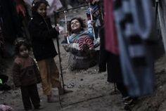 Palestijnse kinderen in Gaza spelen buiten in regenachtig weer. Beeld EPA