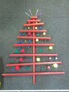 """Sensorial Extension Knobless Cylinders Red Rods A child decided to use """"Counting icicles"""" (spindles) in order to make a star atop the tree. We then got a step stool so the children could see their work from a different perspective."""