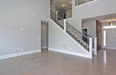 Two story living room with gray staircase railing and gray hardwood floor stain.