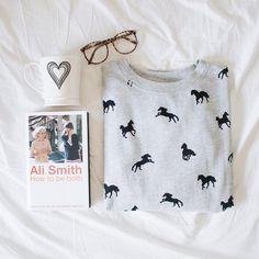 Livro how to be both da Ali Smith, moletom cinza com estampa de unicórnios/cavalos, caneca com coração e um óculos de grau na cama com lençol branco.
