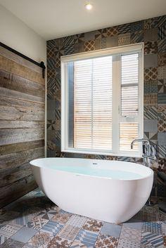 Vue sur une salle de bain avec baignoire contemporaine et carreaux de ciment