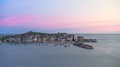 St Ives in Cornwall England was bathed in a quiet violet glow as the sky lightened ahead in the final minutes before dawn.  I woke up early on the first day of our trip to Cornwall as the weather was supposed to be good. When a weather forecast in England says that you take it with a pinch of salt, but seeing as how rare good weather is, you still wake up to peek through the curtains. In this case the forecast was accurate and I reluctantly dragged my tired self out and down to the…