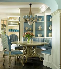 Beautiful curved breakfast nook with built-in shelves & seating with kitchen table & two upholstered country french chairs.