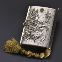The cigarette table rectangular silver embossed and chased from Lehi (a Russian spirit of the forest and trees) among the pines, their set with pink diamonds imitating jelly legs, the top of the lid applied the double-headed imperial eagle gold matches compartment and scraper, dedication inscription inside, flagship of the Grand Cordon of tinder in bud form cabochon purple punch goldsmith Fabergé Imperial privilege, Moscow 1899-1908, 84 zolotniks, by inventory number 15035, 17.5 x12 cm