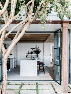 outdoors indoors, open plan living, tree, courtyard, kitchen island, pillars