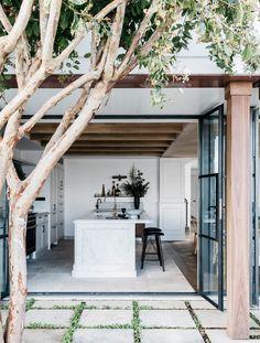 outdoors indoors, open plan living, tree, courtyard, kitchen island, pillars