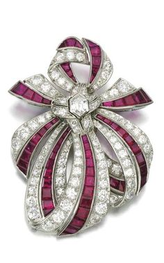 Ruby and diamond brooch, 1950s, of ribbon bow design, set with calibré-cut rubies and brilliant-, single-cut and lozenge-shaped diamonds, fitted case. Via Sotheby's.