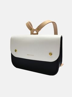 The Ellison Satchel is a gorgeous leather children's school satchel handmade in a small family run factory in Somerset, England. It's the perfect size bag for busy days at nursery, school essentials and stylish journeys. Traditional satchel leather in a bold color blocked black and white, with nude straps. Adjustable shoulder straps and closes securely with two brass poppers on the front flap. 11 x 7.5 x 3.1 inch Made in the UK This school satchel bag is available in lovely colors and…