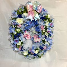 Spring wreath. Plume tailed bird on natural twig perch. Blue hydrangea, bachelor buttons, cream