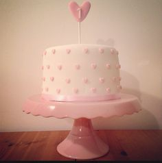 Home made baby girls first birthday cake. White fondant with mini pink hearts decoration. Simple design on pink cake stand.