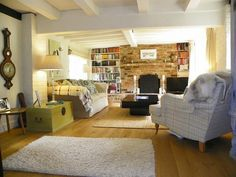photo of comfy cosy rustic beige white exposed brick living room lounge with bookshelves brick fireplace. Interior Design Ideas. Home Design Ideas