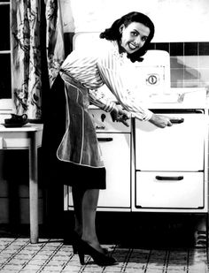 Lena Horne demonstrating how to conserve fuel in the kitchen, 1943.