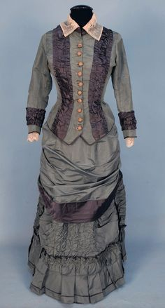 Silk bustle dress,  2-piece sage faille decorated with grey satin bands, semi-boned bodice having dorset buttons, stand collar and cuff trimmed with lace, skirt decorated with ruching and pleats, 1874