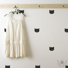 Small black cat shaped silhouette wall decals placed in a patter on a white wall.