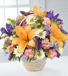 FTD Natural Wonders Bouquet - This garden bouquet displays the bright colors of nature. Arrangement includes orange lilies, purple iris and dainty white daisies, with pink mini carnations and yellow solidago. All are designed in a whitewash handled basket. (Iris may be substituted according to seasons.) Liles may arrive in various stages of development. The lily blooms will continue to open, extending arrangement life - and your recipients enjoyment.