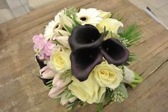 White and dark purple bridal bouquet with calla lilies,tulips, roses, stocks, gerbera daisies, seeded eucalyptus, pines and dusty millers. Designed by Forget-Me-Not Flowers in Banff.