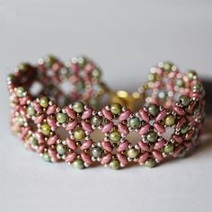 Beadweaving Original Circular Lace Design of Ultraluster Green Glass Beads and Peachy Pink Superduos. Although wide it has a very feminine look