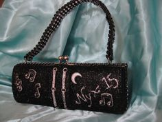 2015: One of my favorites that reflected our Elvis theme! Hard bodied clutch purse with scrapbook moon and scrapbook musical note embellishments, Recollections Ebony and Bling (discontinued) glitters from Michaels; hand-cut ribbon rhinestones from Hobby Lobby on handle. Mystic Krewe of Nyx title float 2015