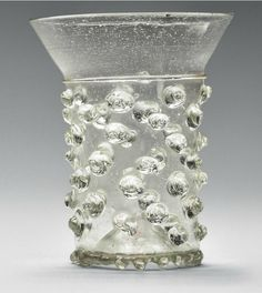A MEDIEVAL GLASS BEAKER (NUPPENBECHER)   LATE 13TH OR 14TH CENTURY, GERMANY OR SWITZERLAND   Of densely seeded pale-green metal, the cylindrical body decorated allover with applied prunts below a trailed thread and flared rim, with a kick-in base, applied to the edge with a pinched footring