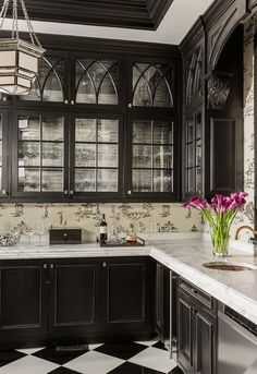 Really cool black and white kitchen with traditional cabinetry. Black and white floor paired with toile wallcoveirng in black and white.