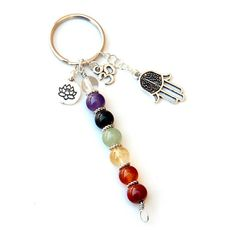 This beautiful Chakra keychain is handmade to order using high quality 8mm round gemstones which represent the seven chakras. It features a silver plated lotus charm, a hamsa charm and an ohm charm all attached to a key ring alongside the chakra pendant. The pendant itself is made