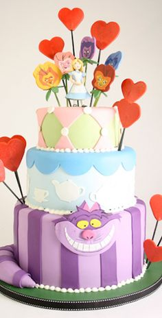 Charm City Cakes - Alice in Wonderland themed cake. Bottom tier is a purple and lavender striped Cheshire Cat. Top tiers are blue and yellow, surrounded by hearts.