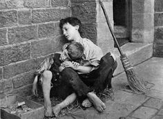 Two barefoot and ragged children sitting on sidewalk. The broom nearby tells me that someone cares enough to keep things tidy, but not enough to help two poor little children. Gross.     United Kingdom    1904