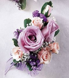 A classic corsage of tea or spray roses in pink and lavender, finsihed with a sheer lavender bow