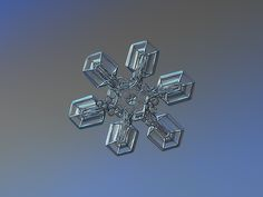Snowflake macro photo: High voltage, medium size snow crystal with broad arms on glass surface with LED back light