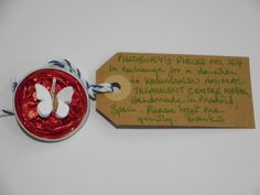 Pillsbury?s Pieces No, 164.  Pin - metallic bright red capsule with white paper butterfly.  In exchange for a donation to KATHMANDU ANIMAL TREATMENT CENTRE, Nepal.  Available at St. George's Church, Madrid on Saturday 13 June from 11.00 - 15.00.